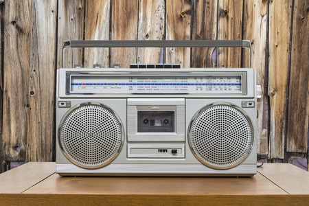 boombox: Vintage boombox on wood table with rustic cabin wood wall. Stock Photo