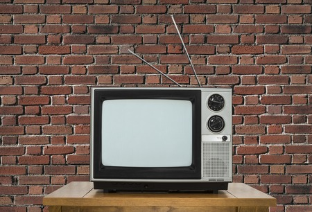 electronic 80s: Old analogue television on wood table with brick wall. Stock Photo