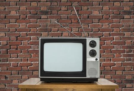 tv: Old télévision analogique sur la table en bois avec mur de briques.