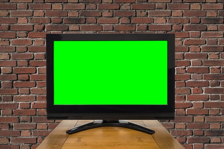 tv set: Modern television with chroma key green screen and red brick wall.