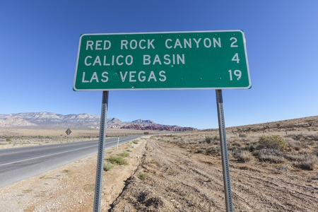red rock canyon: Las Vegas and Red Rock Canyon highway sign with bullet holes. Stock Photo