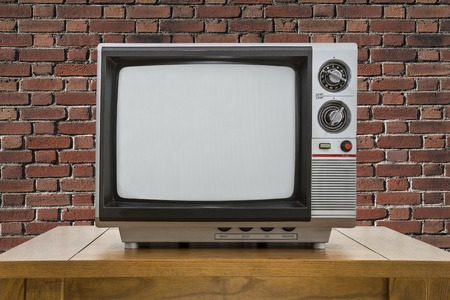 electronic 80s: Vintage portable television and old wood table with red brick wall. Stock Photo