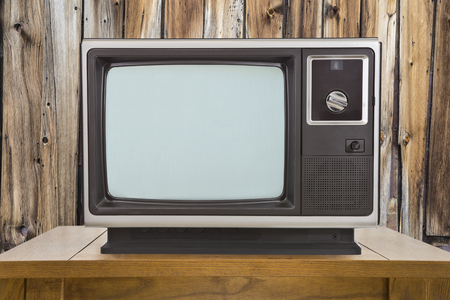 television set: Old television and table with rustic wood wall.