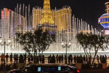 hotel casino: Las Vegas, Nevada, USA - October 10, 2015:  Limo passing line of tourists photographing the Bellagio fountains on the Las Vegas strip.