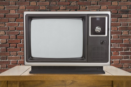 electronic 80s: Old portable television and table with brick wall.