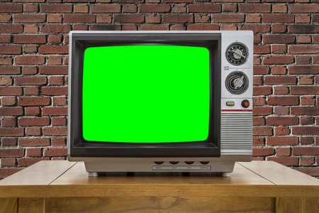 green screen: Vintage portable television with red brick wall and chroma key green screen.