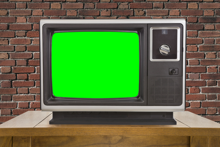 green screen: Old television with chroma key green screen and brick wall.