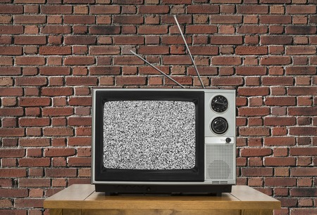 static: Old analogue television with static screen and brick wall. Stock Photo