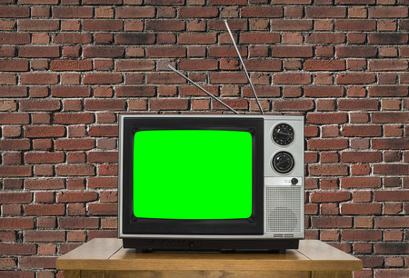 green screen: Old analogue television with chroma key green screen and brick wall.