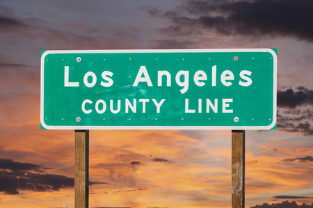 los angeles county: Los Angeles county line sign with sunset sky.