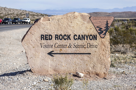 red rock: Las Vegas, Nevada, USA - November 27, 2015:  Red Rock Canyon visitor center sign with holiday traffic highway line up near Las Vegas, Nevada.