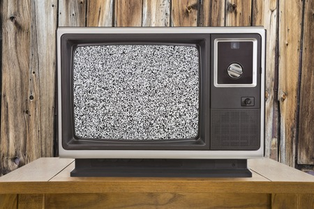 old fashioned tv: Old portable television with static screen and rustic wood wall.