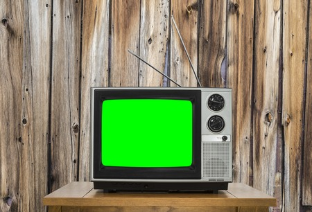 green screen: Vintage television with rustic wood wall with chroma key green screen.