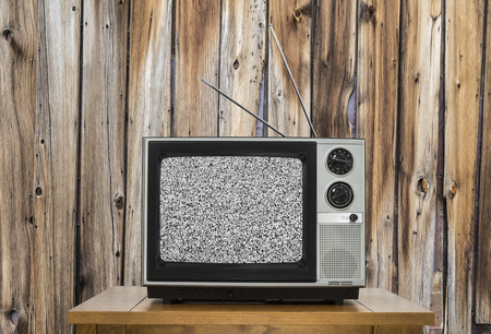 old fashioned tv: Vintage television with rustic wood wall and static screen.