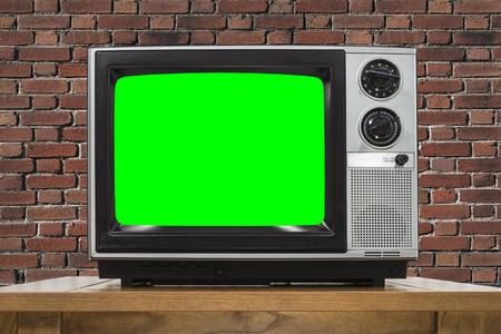 green screen: Analog television with brick wall and chroma key green screen.