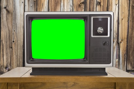 electronic 80s: Old television with chroma key green screen and rustic wood wall.