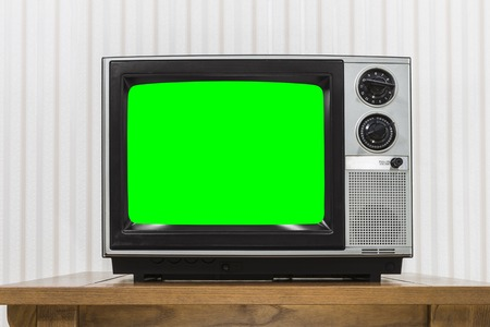 Old portable television set on vintage wood table with chroma key green screen.