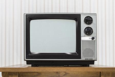 television set: Old portable television set on vintage wood table.