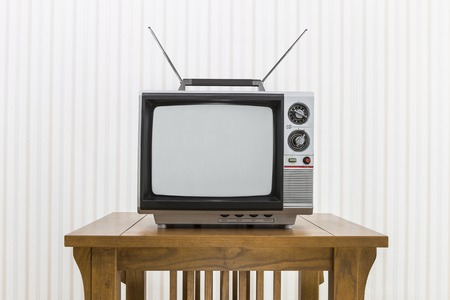 old fashioned tv: Old portable television with antenna on wood table.