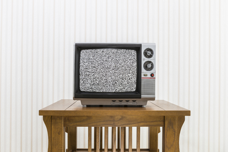 old fashioned tv: Old portable television on wood table with static screen