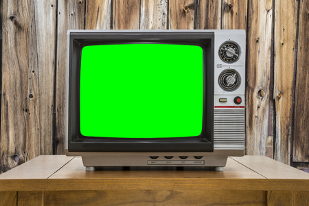 green screen: Vintage portable television with chroma key green screen and rustic cabin wall. Stock Photo