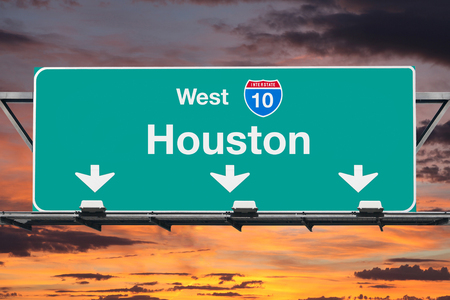 Houston Interstate 10 west highway sign with sunrise sky.
