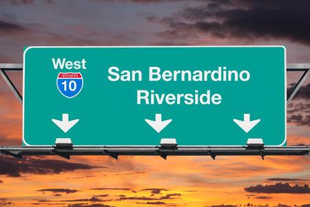 日の出の空でサン バーナーディーノ リバーサイド インターステート 10 西高速道路標識です。