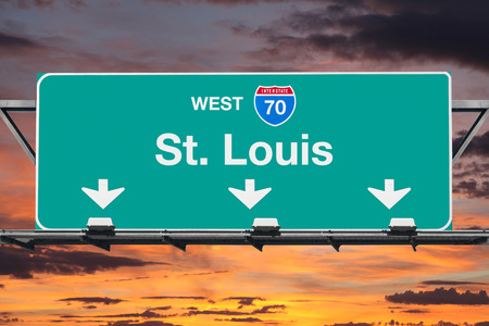 st louis: St Louis Interstate 70 west highway sign with sunrise sky.