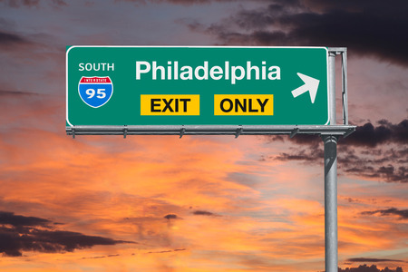 highway sign: Philadelphia exit only highway sign with sunrise sky.