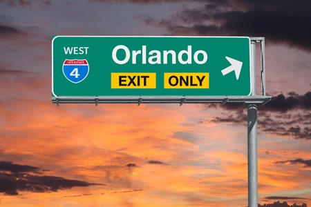 fl: Orlando Florida exit only freeway sign with sunrise sky.