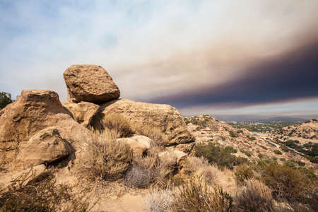 northridge: Southern California Los Angeles area sandstone rock formations with dark brush fire smoke filled sky.