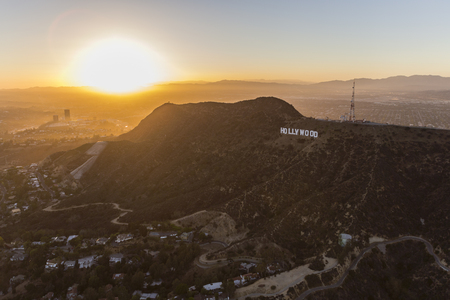 san fernando valley: Los Angeles, California, USA - July 21, 2016:  Aerial of sun setting behind the Hollywood Sign on Mt. Lee in Griffith Park.