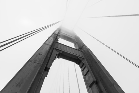 fog white: Golden Gate bridge tower emerging from iconic San Francisco bay fog bank in black and white.