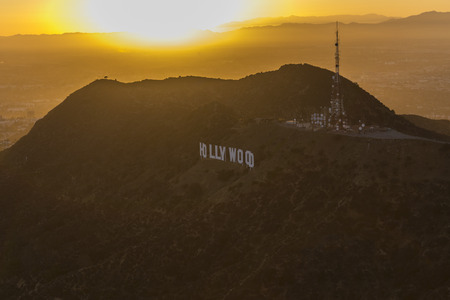 hollywood hills: Los Angeles, California, USA - July 21, 2016:  Hollywood Sign with setting sun aerial in Griffith Park.