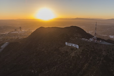 san fernando valley: Los Angeles, California, USA - July 21, 2016:  Aerial of sun setting behind the Hollywood Sign in Griffith Park.