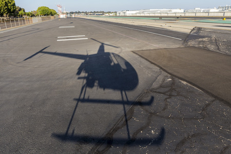 Helicopter shadow on airport  taxiway tarmac.