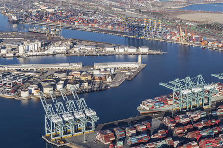 literas: Los Angeles, California, USA - August 17, 2016:  Afternoon aerial view of Los Angeles harbor berths, cranes and containers.