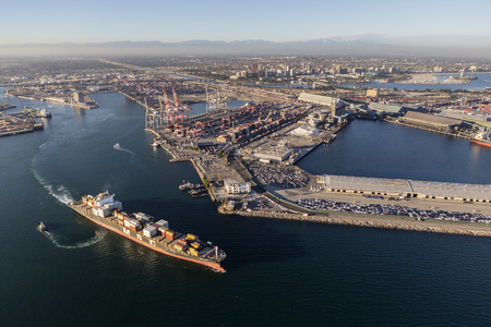 Long Beach, California, USA - August 16, 2016: Afternoon aerial view of busy container cargo facilities and passing ship. Editorial