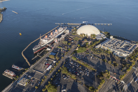 neighboring: Long Beach, California, USA - August 16, 2016:  Afternoon aerial view of the Queen Mary and neighboring cruise ship terminal dome in Long Beach Harbor.