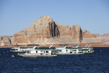lake powell: Desert sandstone peaks and houseboats on Lake Powell in the Glen Canyon National Recreation Area.