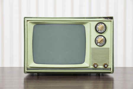 Grungy green vintage television set on table.