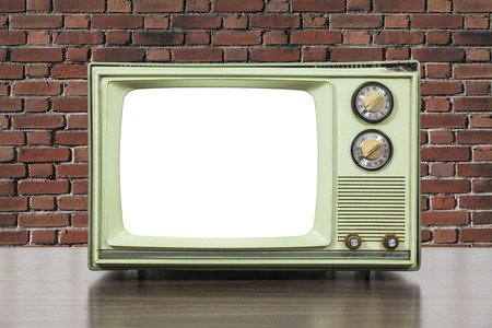 television set: Grungy green vintage television set with brick wall and cut out screen.