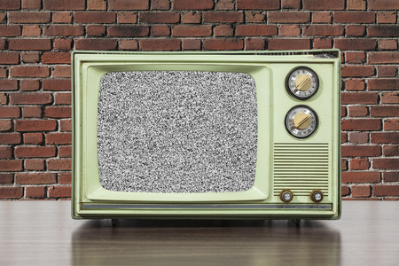 television set: Grungy green vintage television set with brick wall and static screen.
