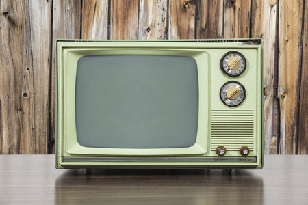 television set: Grungy green vintage television set with old wood paneling. Stock Photo
