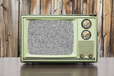 television set: Grungy green vintage television set with wood wall and static screen.