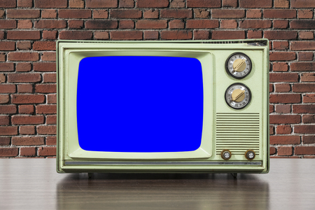 television set: Grungy green vintage television set with brick wall and chroma key blue screen. Stock Photo