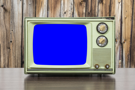 television set: Grungy green vintage television set with wood wall and chroma key blue screen.