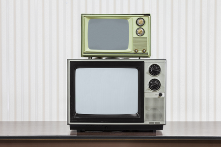 Two vintage televisions stacked on table.
