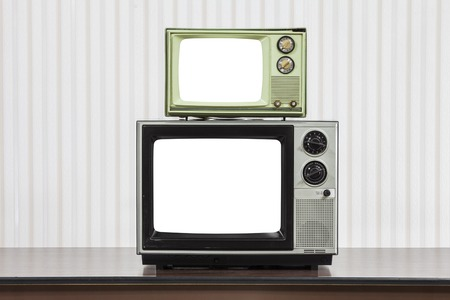 Two vintage televisions stacked on table with cut out screens.