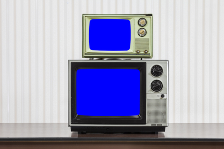 Two vintage televisions stacked on table with chroma key blue screens. 版權商用圖片